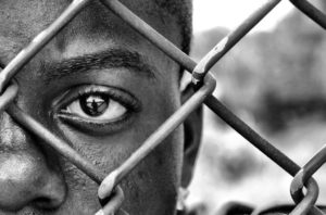 Uomo nero dietro una una rete